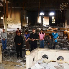 Assyrian Christians return to their church building to pray after Islamic extremists destroyed it.